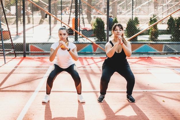 Бодипозитивная женщина делает упражнения со своей девушкой в спортивном парке по утрам.