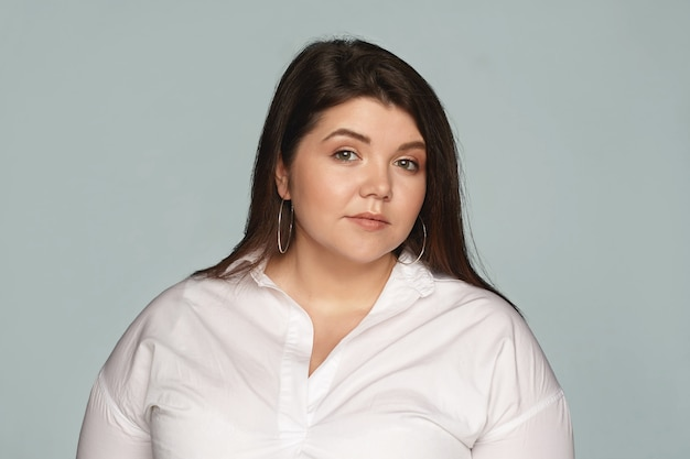 Body positivity, femininity, beauty, cosmetics and fashion concept. picture of attractive gorgeous young chubby woman dressed in white shirt posing