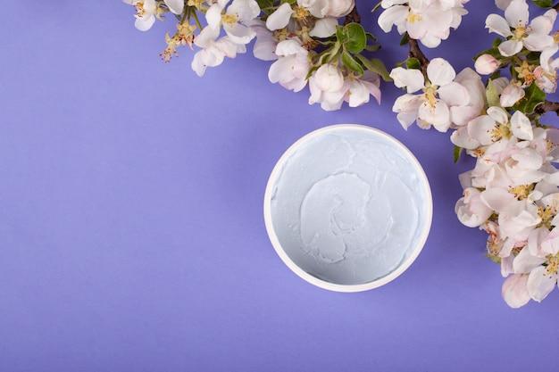 紫色の背景に白い花を持つボディスクラブコピースペースクローズアップトップビュー。美容、シワ予防、スキンクリーニング、ボディケア化粧品