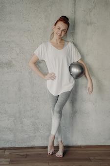 바디 쉐이핑. 필라테스나 바레 운동 후 작은 은색 핏볼을 가진 젊고 아름다운 스포티 여성의 전신 샷