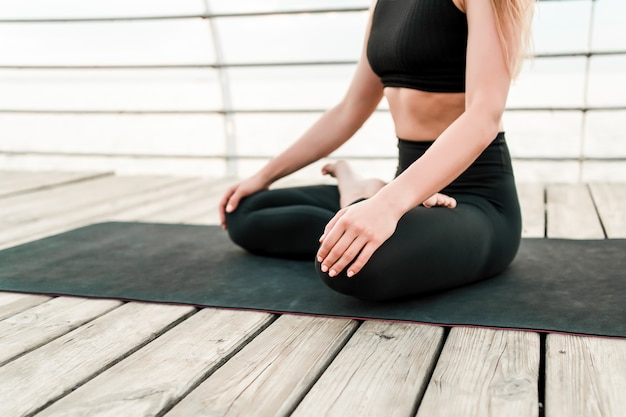 Body shot of a woman meditating near the sea in the morning