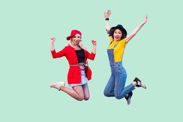 세련된 옷을 입은 두 명의 행복한 비명을 지르는 세련된 힙스터 소녀의 신체 크기 초상화가 공중으로 뛰어오르고 팔을 들고 카메라를 쳐다보고 있습니다. 실내 스튜디오 촬영, 녹색 배경에 고립
