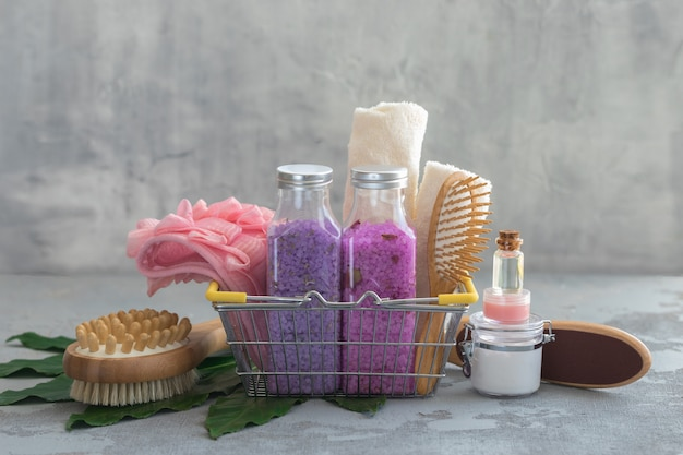 Body spa treatment bamboo brushes with bath salt, cream, oil, towels in a shop basket