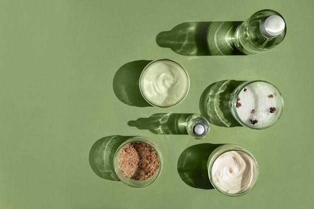 緑の背景の女性のボディトリートメントとスパコンセプトのスクラブマスククリームと天然オイル化粧品...