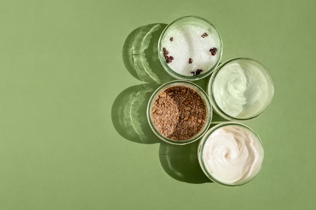 Body treatment and spa concept scrub mask cream and natural oil cosmetics on green background womans...