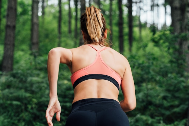 Body of a women running through a lush green forest with many trees