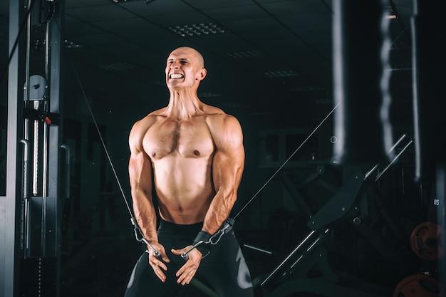 Bodybuiderは、ジムでクロスオーバー運動を実演します。