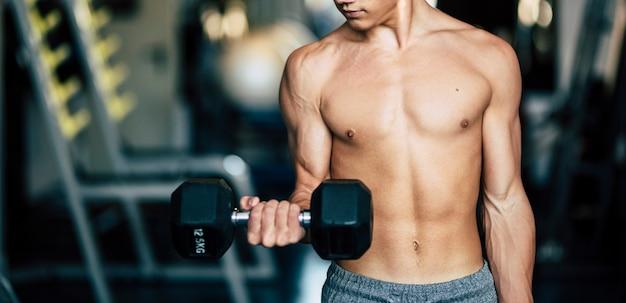 보디빌더는 티셔츠 없이 조용히 체육관에서 근육을 훈련합니다 - 아령을 들고 있는 팔을 바라보고 있습니다