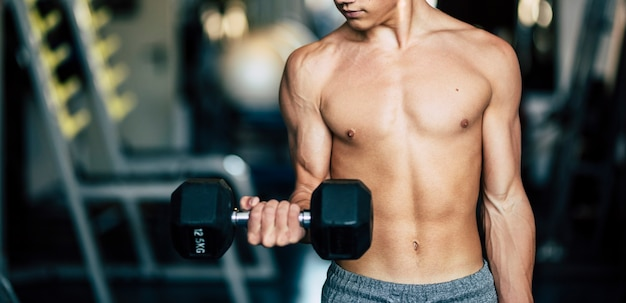 Bodybuilder alone training his muscles at the gym in silence and without t-shirt - looking at his arm holding a dumbbells