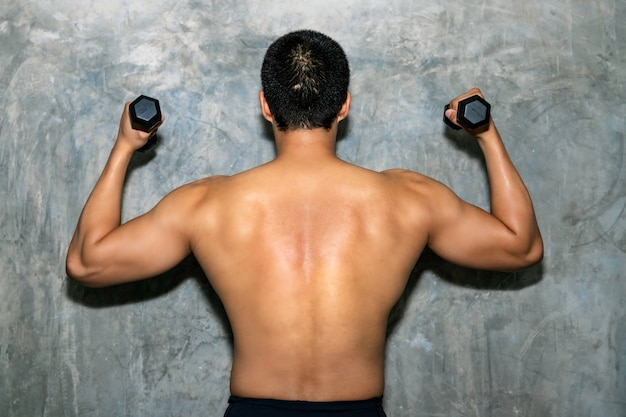 Bodybuilder athletic asian man posing with bumbbell back muscles, triceps and latissimus on background.