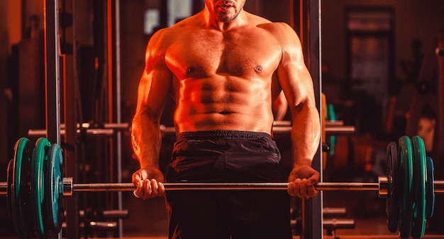 Бодибилдер спортивный мужчина с шестью пакетами, идеальным прессом, плечами, бицепсами, трицепсами, грудью. тренировка со штангой. спортивный (ый) парень, стоя со штангой, тренировки в тренажерном зале.