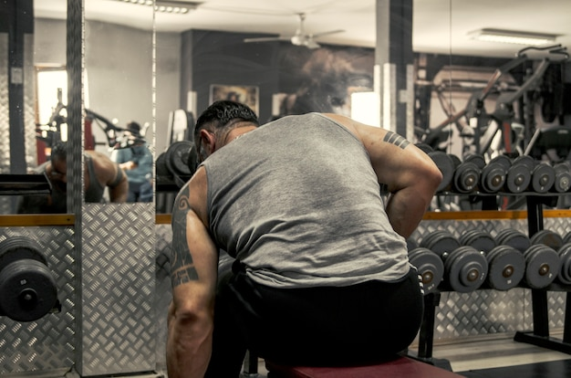 Bodybuilder back of man in sweat t shirt prepare for new training in gym