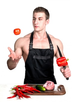 The bodybuilder cook prepares a lunch of vegetables and meat.
