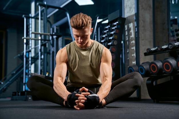 Bodybuilder doing butterfly stretch on floor in gym.