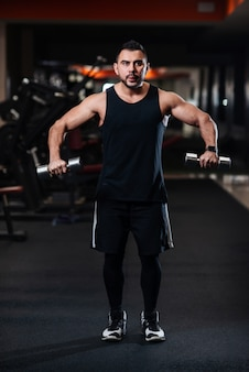 Bodybuilder doing exercise for the shoulder muscles, deltoid with dumbbell in the gym