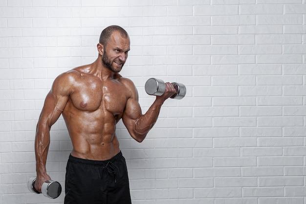 Культурист делает упражнения на бицепс с гантелями у кирпичной стены.