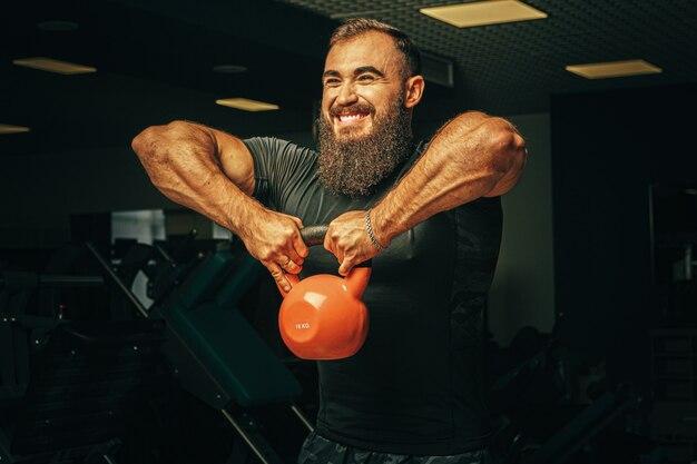 Культурист делает упражнения с гантелями в темном тренажерном зале