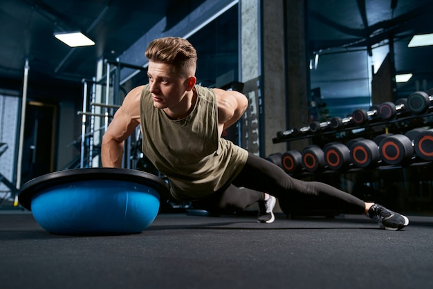 Bodybuilder doing push ups on one hand.