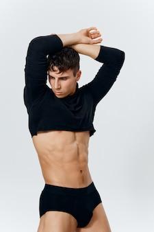 Бодибилдер фитнес-мужчина с накачанным торсом и черными трусиками модельный свитер