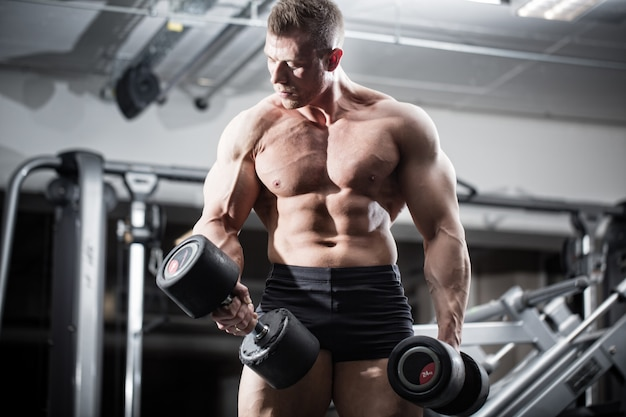Bodybuilder in gym at fitness training with barbells