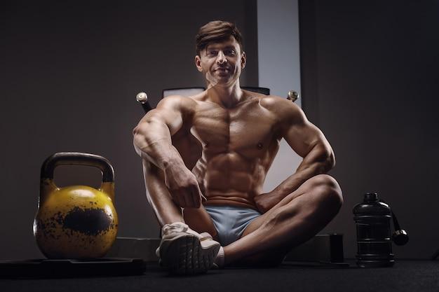ケトルベルの隣にボディービルダーハンサムな強い運動男。トレーニングフィットネスとボディービルの健康的な概念の背景