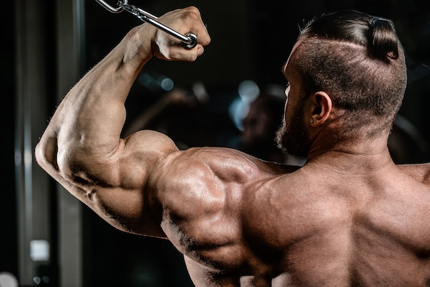 Bodybuilder handsome strong athletic man pumping up biceps muscles workout fitness and bodybuilding concept background - muscular fitness men doing arms exercises in gym naked torso