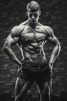 Культурист красивый сильный спортивный грубый мужчина накачивает мышцы пресса, тренировки, фитнес и концепция бодибилдинга