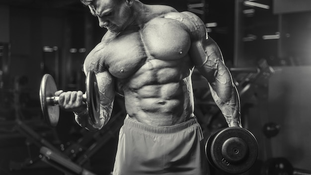 Bodybuilder handsome strong athletic rough man pumping up biceps muscles workout fitness and bodybuilding concept