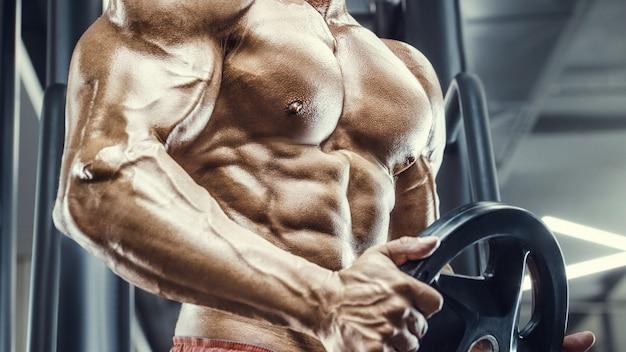 ボディービルダーハンサムな強い運動ラフ男は、筋肉のトレーニングフィットネスとボディービルの健康的な概念の背景をポンプアップします-