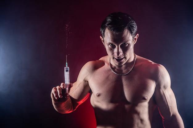 Культурист, держащий большой шприц с инъекцией. понятие стероида в спорте и наркомании.