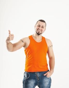 Культурист в джинсах и оранжевой рубашке делает жест рукой большой палец вверх.