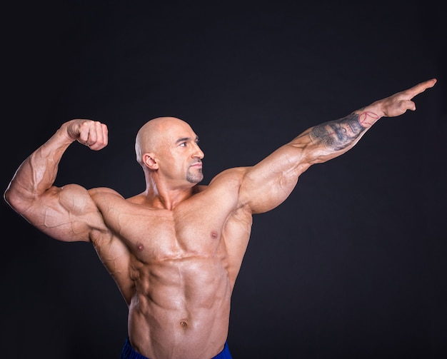 Bodybuilder is posing, showing his muscles.
