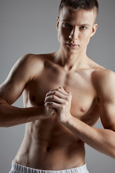 Bodybuilder joined hands near chest on gray background copy space