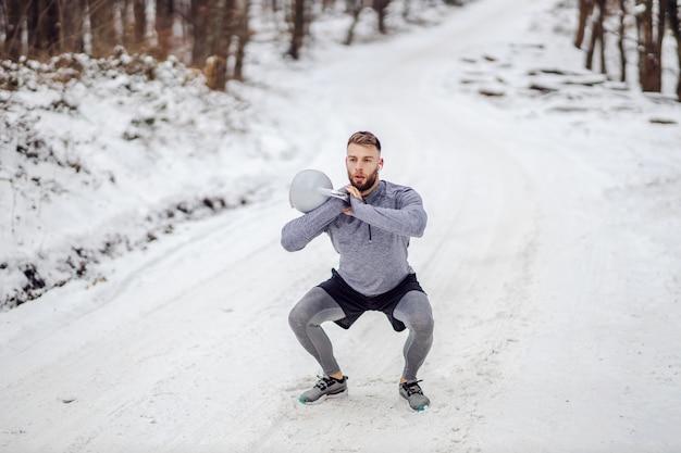 冬の雪道で森の中でしゃがみながらケトルベルを持ち上げるボディービルダー。ボディービル、ウィンタースポーツ、フィットネス