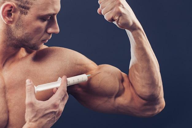 Культурист делает инъекцию витаминов. фотография спортивного мужчины с идеальным телосложением на темном фоне