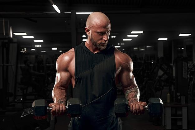 ダンベルで上腕二頭筋をトレーニングするボディービルダーの男性モデル。黒のシャツのモデル