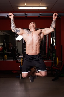 Bodybuilder man performing workout at the gym