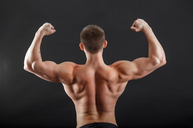 A bodybuilder man posing turn his back