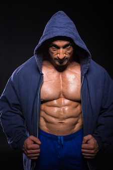 Bodybuilder man put on his jacket and posing.