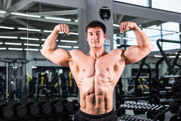 체육관에서 완벽한 팔뚝, 삼두근 및 가슴을 가진 보디 빌딩 남자.