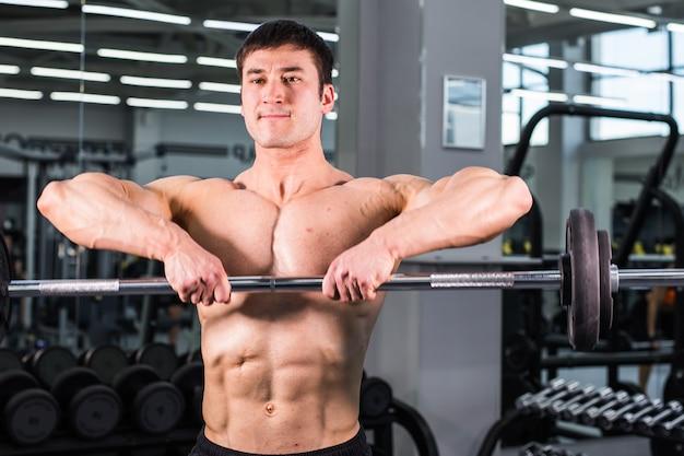 체육관에서 완벽한 팔뚝, 삼두근 및 가슴을 가진 보디 빌딩 남자