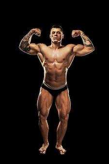 ボディービルダーのポーズ。美しいスポーティな男の男性の力。フィットネス筋肉ボディ。黒の背景に分離