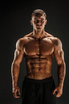 Bodybuilder posing  fitness muscled man on dark scene