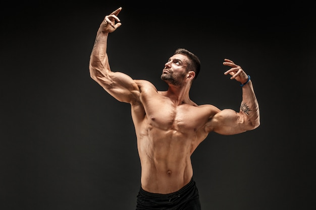 Bodybuilder posing. fitness muscled man on dark wall.