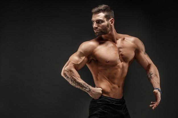 ボディービルダーのポーズ。暗い壁にフィットネス筋肉男。