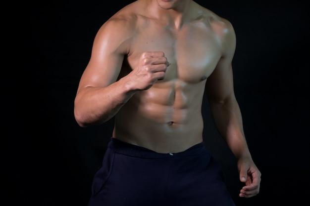 Bodybuilder posing muscular body on black background