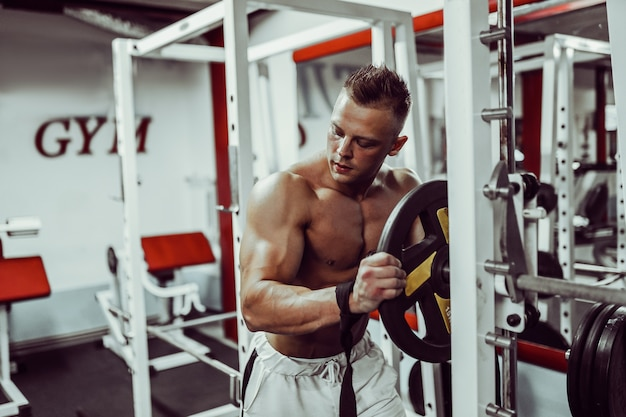 Bodybuilder preparing for exercise with barbell in gym