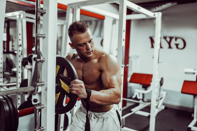 Bodybuilder preparing for heavyweight exercise with barbell in gym