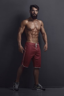 Bodybuilder in red shorts on wall background. with copy space
