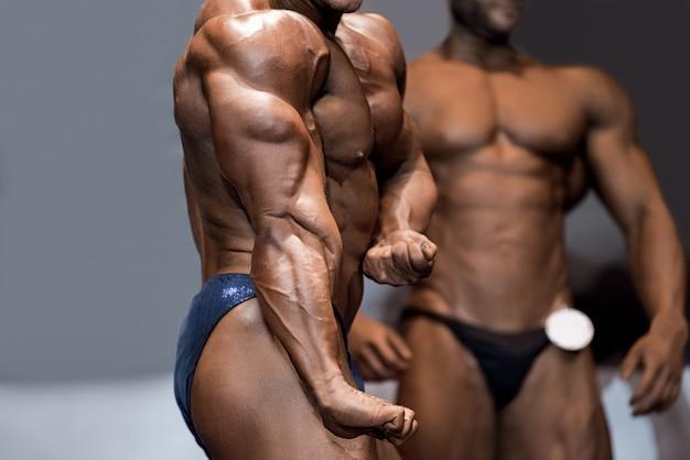 ボディービルダーのサイドトライセップポーズ。ステージ上で屈曲する筋肉アスリート。彼の最初の競争。審査員は興奮しています。